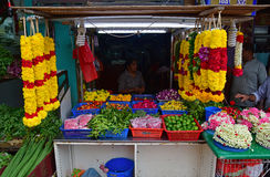 Indian stall selling different flower buds on the table basket, green lime, leaves and colourful garland nearby Hindu temple Royalty Free Stock Photo