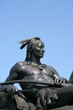 Indian Statue. A statue of a native american indian with feathered headdress sitting back holding a bow and arrow Royalty Free Stock Photography