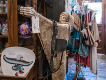 Indian statue and old leather harness for sale in flea market. Tucson, AZ, March 22, 2016: Statue of Indian and old leather harness for sale among other jumble stock images