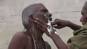 Indian street barber shaving hindu brahman monk using an open razor blade on a ghat of sacred river Ganges stock video