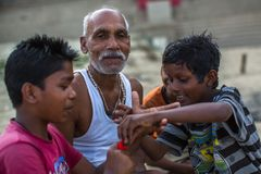 Indian street children and a grown man on the banks of Ganga river. Royalty Free Stock Photography