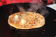 Indian street Food. Making of veg Parantha with butter, A fried stuffed bread Royalty Free Stock Photography