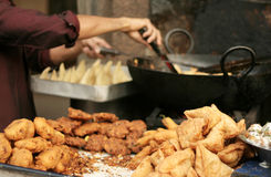 Indian street food vendor make popular samosas on a busy road Royalty Free Stock Image