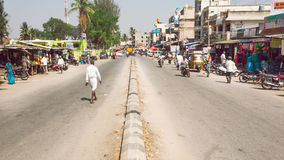 Indian street with pedestrian on wide area with stores and customers of small town in Karnataka state Royalty Free Stock Photo