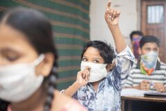 Indian students raise hand studying In classroom wearing mask maintaining social distancing looks at camera, school reopen during