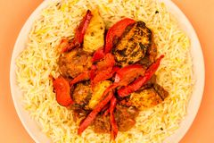 Indian Style Chicken Jalfrezi Curry And Pilau Rice. Against An Orange Background Royalty Free Stock Images