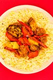 Indian Style Chicken Jalfrezi Curry And Pilau Rice. Against A Red Background Stock Photo