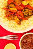 Indian Style Chicken Jalfrezi Curry And Pilau Rice. Against A Red Background With A Sweet Chilli Dipping Sauce And Fresh Lime Royalty Free Stock Photos
