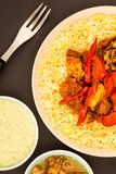 Indian Style Chicken Jalfrezi Curry And Pilau Rice. Against A Black Background With Mango Chutney And A Dipping Sauce Royalty Free Stock Image