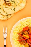 Indian Style Chicken Jalfrezi Curry And Pilau Rice. Against An Orange Background With Naan Bread Royalty Free Stock Images