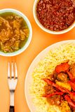 Indian Style Chicken Jalfrezi Curry And Pilau Rice. Against An Orange Background With Sweet Chilli And Dipping Sauces Royalty Free Stock Photo