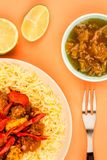 Indian Style Chicken Jalfrezi Curry And Pilau Rice. Against An Orange Background With Mango Chutney And Fresh Lime Stock Photo
