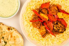 Indian Style Chicken Jalfrezi Curry And Pilau Rice. Against A Pink Background With naan Bread And A Dipping Sauce Stock Images