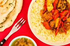 Indian Style Chicken Jalfrezi Curry And Pilau Rice. Against A Red Background With Naan Bread And Mango Chutney Royalty Free Stock Photography