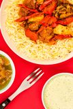 Indian Style Chicken Jalfrezi Curry And Pilau Rice. Against A Red Background With Mango Chutney And A Dipping Sauce Stock Images