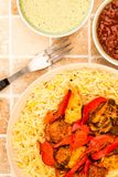 Indian Style Chicken Jalfrezi Curry And Pilau Rice. On A tiled Kitchen Table Top With Dipping Sauces Royalty Free Stock Images
