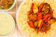Indian Style Chicken Jalfrezi Curry And Pilau Rice. On A tiled Kitchen Table Top With Mango Chutney And Dipping Sauce Royalty Free Stock Photos