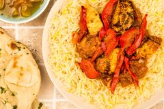 Indian Style Chicken Jalfrezi Curry And Pilau Rice. On A tiled Kitchen Table Top With Naan Bread And Mango Chutney Royalty Free Stock Photography