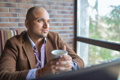 Indian stylish man drinking coffee, dreamy looking up and thinking Royalty Free Stock Images