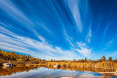 Indian summer. Cirrus clouds are reflected in the Winnipeg River. Wonderful autumn day. Old Pinawa Dam Park. The concept of ecological and recreational tourism Stock Photo
