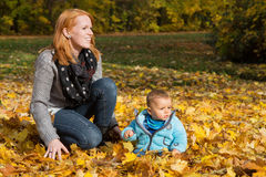 Indian summer: Young woman with her baby in autumn. Family conce Royalty Free Stock Images