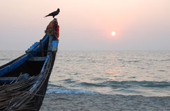 Indian sunset. Sunset on the beach in India with traditional fishermen's boat in foreground Stock Photos