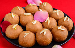 Indian Sweet Besan Ladoo. Vegan Besan Ladoo on red background Royalty Free Stock Photography