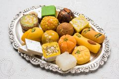 Indian sweets for diwali festival or wedding, selective focus. Stock photo of Indian sweets served in silver or wooden plate. variety of Peda, burfi, laddu in stock photo
