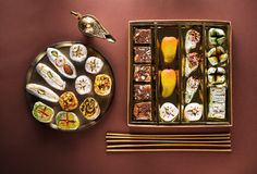 Indian sweets and Mithai in a box and a plate, insense sticks and Aladdin lamp. Stock Photos