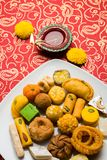 Indian sweets or Mithai for diwali festival with oil lamp or diya and gift box. Stock photo of Indian sweet or mithai and oil lamp or diya with gift box and Stock Photo