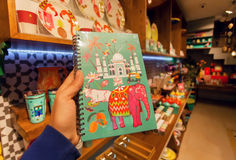 Indian symbols - Taj Mahal, cow and elephant on cover of notebook in souvenir store. BANGALORE, INDIA - FEB 14: Indian symbols - Taj Mahal, cow and elephant on Stock Photos
