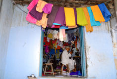 Indian tailor, India. Traditional tailor shop in Jaipur, India displaying colourful fabrics and clothing Stock Images