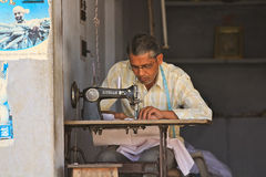 Indian Tailor. JAIPUR, INDIA, MARCH 4: An unidentified tailor at work in his street side shop on March 4, 2012 in Jaipur, Rajasthan, Northern India Stock Photos