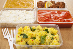 Indian Takeaway Food. A selection of Indian takeaway food in plastic containers on a wooden table. Aloo saag (potato spinach curry), chicken tikka masala royalty free stock images