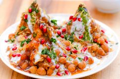 Indian snacks- chole samosa chaat. Indian tea time snacks- chole chaat made of boiled chickpea curry ,samosa,curd,mint chutney and tamarind chutney Stock Images