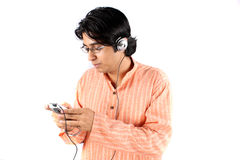 Indian Teen with MP3. An Indian teenage boy in a traditional attire, listening to music on his MP3 player, on a white background Stock Image