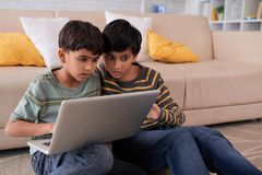 Boys with laptop. Indian teenage boys watching something interesting on laptop screen Stock Photos