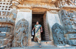 Indian temple entrance and woman in sari coming past 12th century sculptures Stock Images