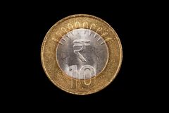 Indian ten rupee coin close up on black. An extreme close up of an Indian ten rupee coin on a solid black background Royalty Free Stock Image