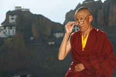 Indian tibetan monk sadhu. Indian tibetan old monk in red color clothing with glasses in front of monastery Royalty Free Stock Image