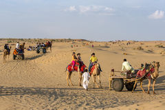 Indian tourists  riding camels in Thar desert, Rajasthan, India. Jaisalmer, India - March 13, 2016: Indian tourists  riding camels in Thar desert, Rajasthan Royalty Free Stock Photos