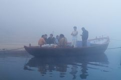 Indian tourists  sailing on boat on the river Ganges at cold foggy winter morning. Varanasi Stock Photos