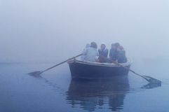 Indian tourists  sailing on boat on the river Ganges at cold foggy winter morning. Varanasi Royalty Free Stock Photo