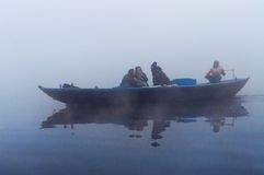 Indian tourists  sailing on boat on the river Ganges at cold foggy winter morning. Varanasi Royalty Free Stock Photography