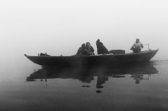 Indian tourists  sailing on boat on the river Ganges at cold foggy winter morning. Varanasi Stock Image