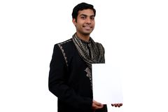 Indian in traditional clothes. Indian in traditional clothes holding a white board in hand. Clipping path available Stock Photo