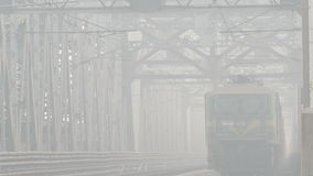 Indian train bridge 4k. KOLKATA, INDIA - MARCH, 2017: train cross the bridge over the Hooghly river in foggy atmosphere in Kolkata, India on March, 2017 stock video footage