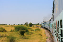 Indian train driving through across the plain. Royalty Free Stock Photos