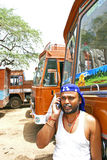 Indian truck driver talking on his mobile phone with trucks parked on his back. Mobiles in India Royalty Free Stock Image