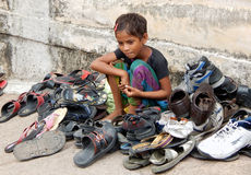 Indian unidentified girl watching the foot wear out side the Hindu temple Stock Photography